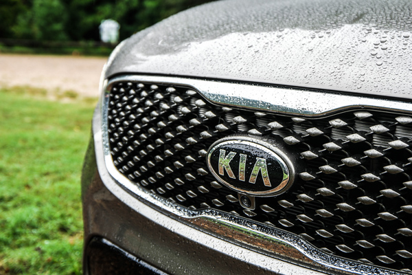 Jeff-Bogle-NX500-16-50S-Kia-logo-and-grill-close-up-in-rain