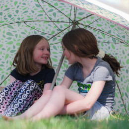 Sisters Together Beneath an Umbrella in Spring